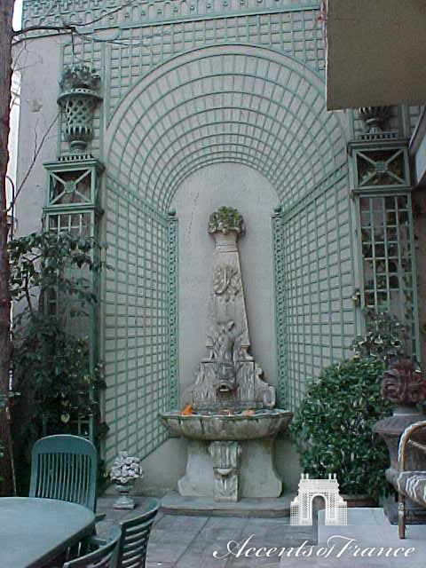 Custom latticework designed to create a focal point around a fountain with the use of a trompe l'oeil panel.